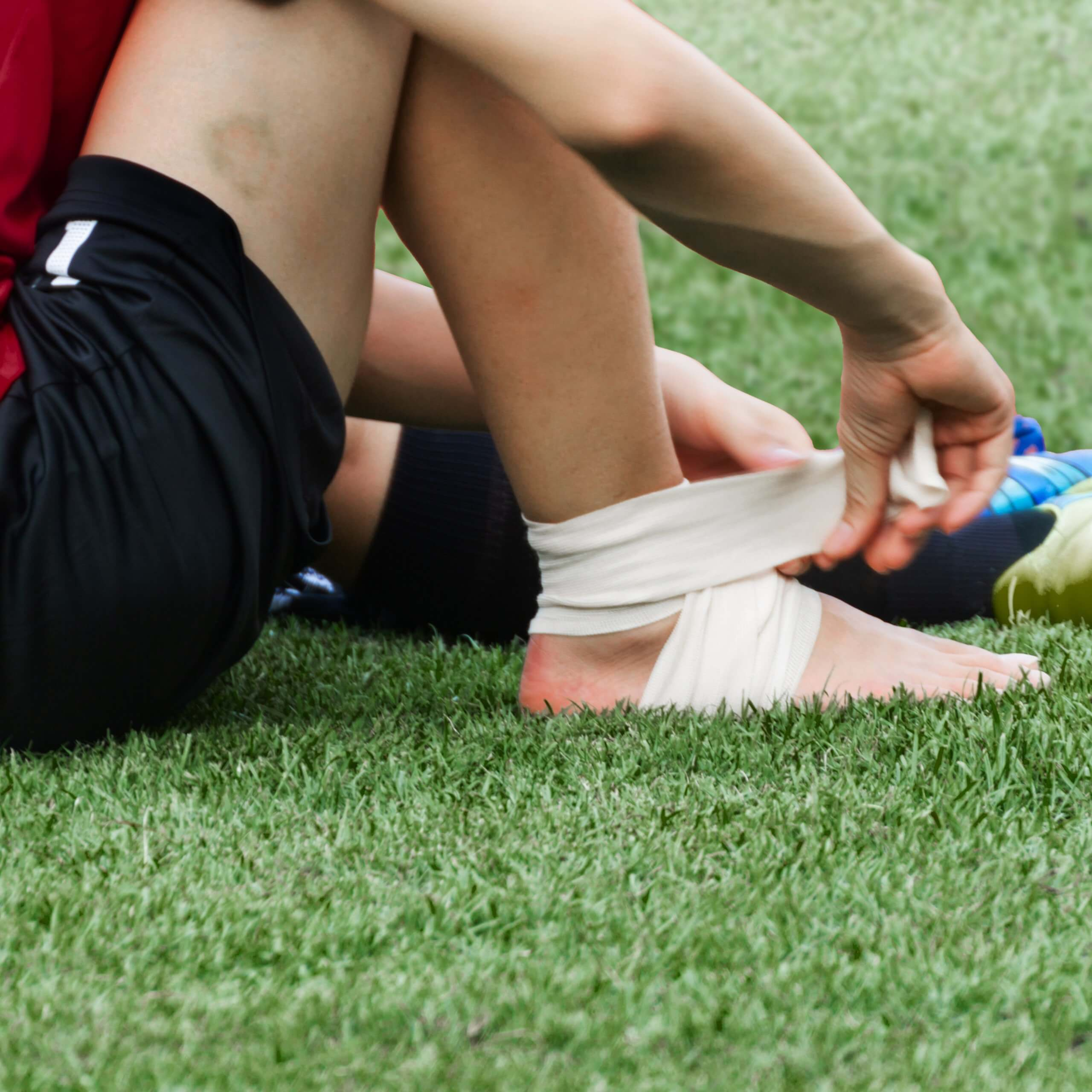man applying compression bandage onto ankle injury of a football